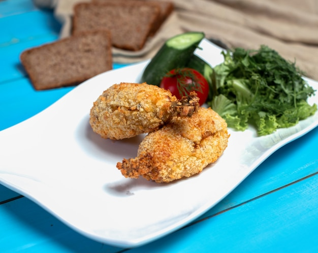Crispy fried chicken legs with green salad. Free Photo