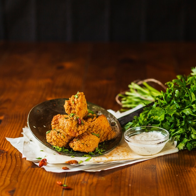 Crispy fried chicken nuggets on an old skimmer with garlic dip and fresh coriander Free Photo