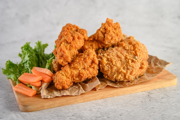 Crispy fried chicken on a wooden cutting board Free Photo