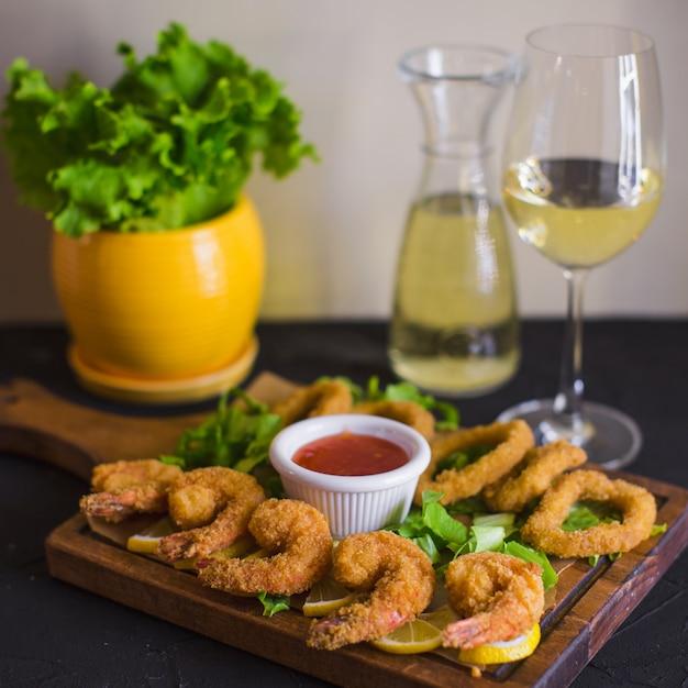 Crispy fried shrimps and calamaris served with lemon and sweet chili sauce Free Photo