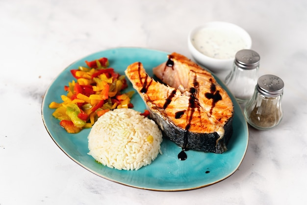 Crispy grilled salmon steak with steamed paprika and rice Premium Photo