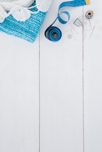 Crochet and knitted fabric; measuring tape; pushpin; thimble; thread and button on wooden table Free Photo