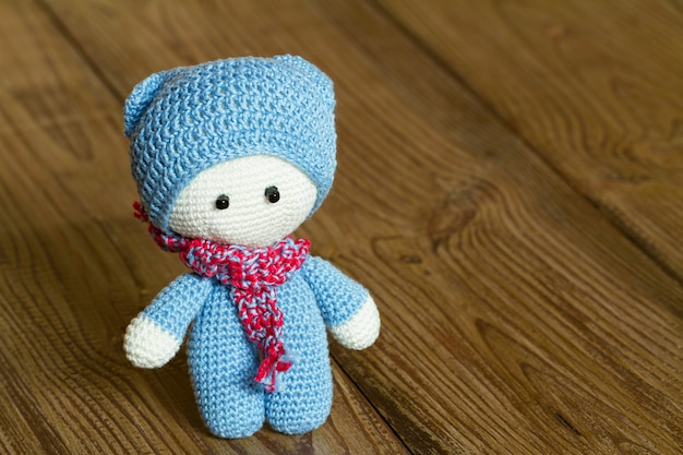 Crochet soft toy on a wooden background Premium Photo