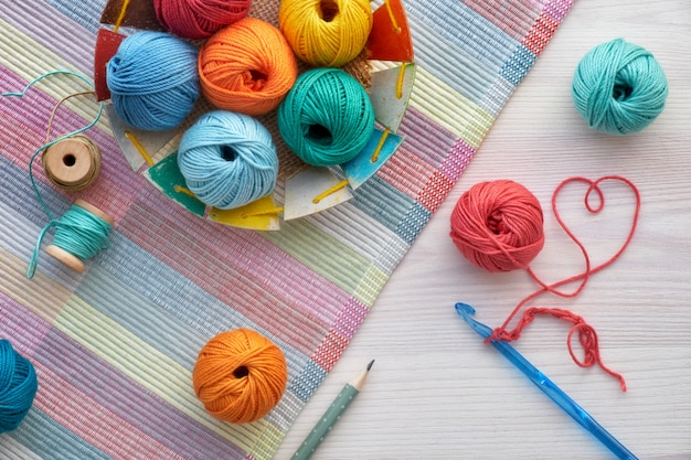 Crochet and yarn balls, top view on light wood Premium Photo