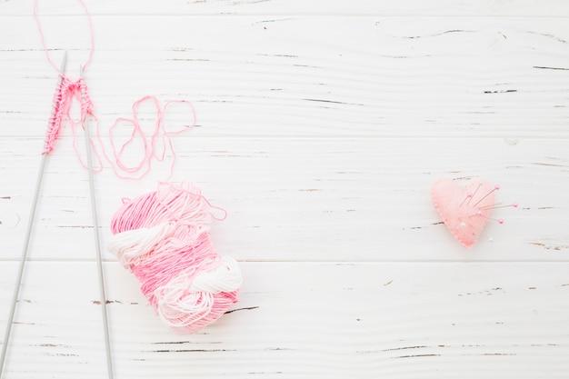 Crochet and yarn near sewing pins in pink heart shape cushion Free Photo
