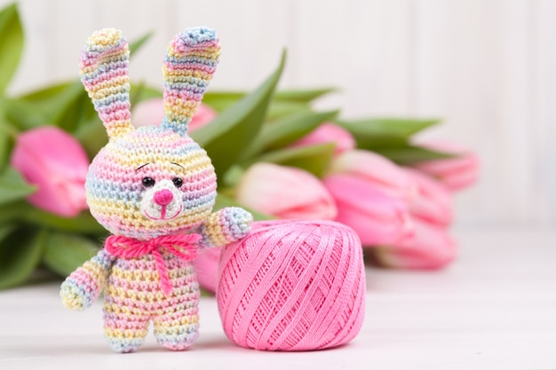 Crocheted rabbit with delicate pink tulips. easter concept. knitted toy, handmade, needlework, amigurumi. Premium Photo