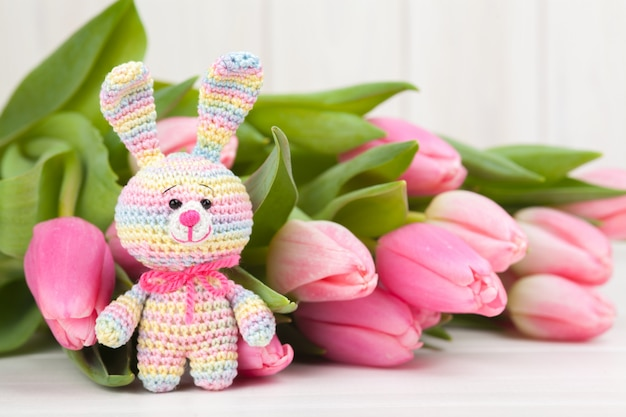 Crocheted rabbit with delicate pink tulips. knitted toy, handmade, needlework, amigurumi. Premium Photo