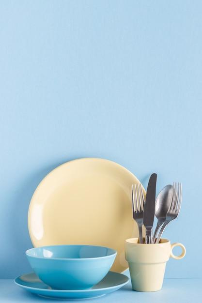 青いパステルカラーの背景に食器とカトラリー Premium写真
