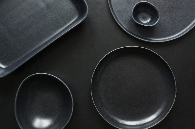 Crockery, clayware, black utensils and different stuff on black tabletop. Premium Photo