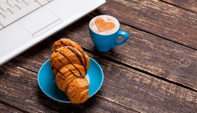 Croissant and cup of coffee with laptop on wooden table. Premium Photo
