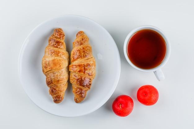 Круассан в тарелке со сливами, чайная кладка Бесплатные Фотографии