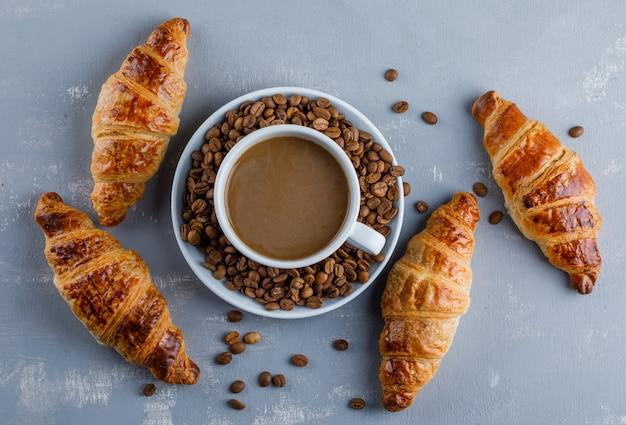 一杯のコーヒー、コーヒー豆、フラットとクロワッサンが横たわっていた。 無料写真