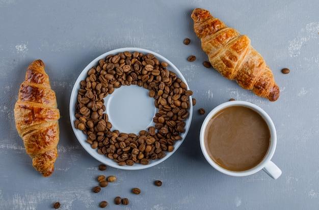 Круассан с чашкой кофе, кофе в зернах, плоская планировка. Бесплатные Фотографии