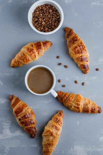 一杯のコーヒー、コーヒー豆、上面とクロワッサン。 無料写真