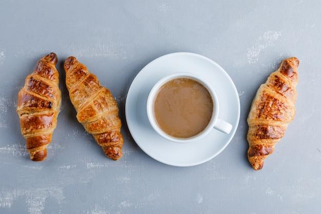 一杯のコーヒーとクロワッサン、フラットが横たわっていた。 無料写真