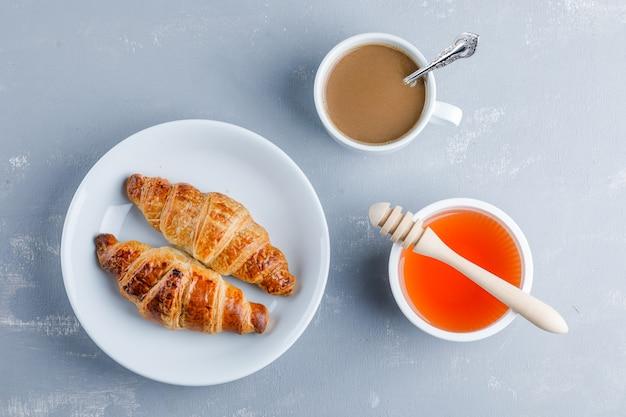 Круассан с чашкой кофе, медом, ковш в тарелке, плоская кладка. Бесплатные Фотографии
