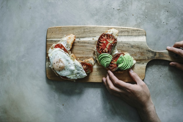 Croissant with heirloom tomato, avocado, and a fried egg Free Photo