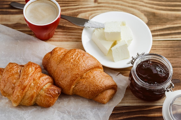 Croissants, butter and coffee on a wooden table Premium Photo
