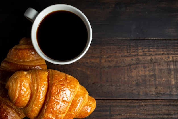 Croissants and coffee on old wood table. Free Photo