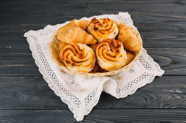 Croissants and cupcake in the basket over the lace napkin over the wooden backdrop Free Photo