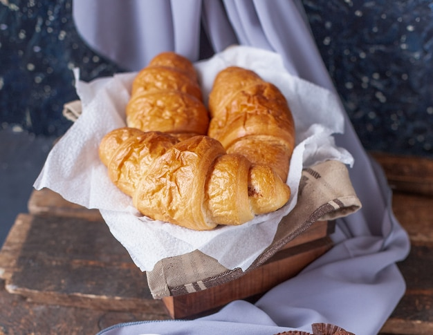 Croissants inside a wooden box on a piece of white tissue Free Photo