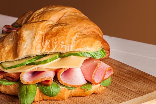 木製のまな板にクロワッサンサンドイッチ 無料写真