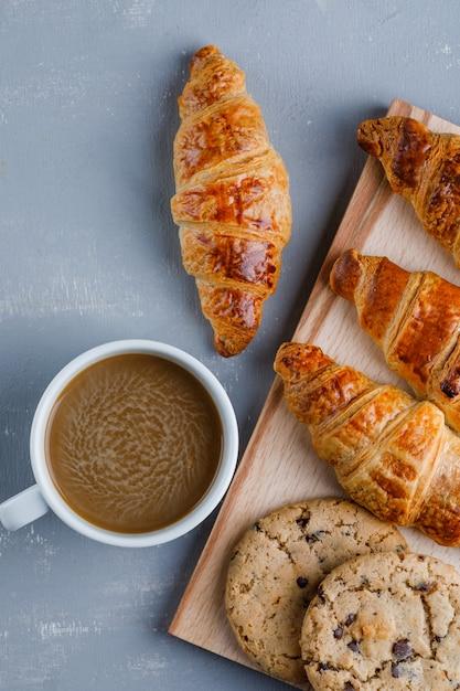 一杯のコーヒーとクロワッサン、クッキーフラットは石膏とまな板の上に置く 無料写真