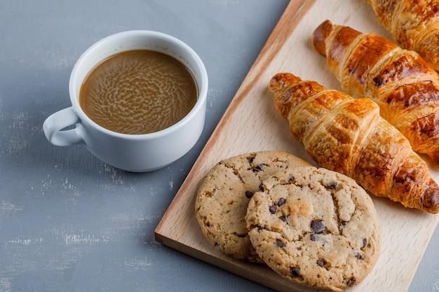 一杯のコーヒー、クッキーと石膏とまな板の上の高角度のビューのクロワッサン 無料写真
