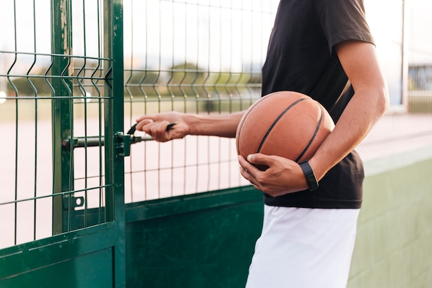 Crop anonymous athlete male opening basketball court Free Photo