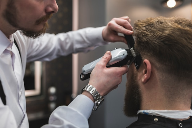 Crop barber shaving temples of man 23 2147778756
