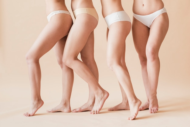 Crop barefoot female figures in underwear standing behind each other Premium Photo