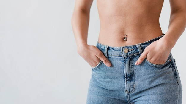 Crop of belly of woman in denim Free Photo