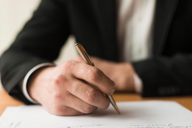 Crop businessman writing on paper Premium Photo