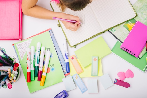 Crop child at table with school supplies Free Photo