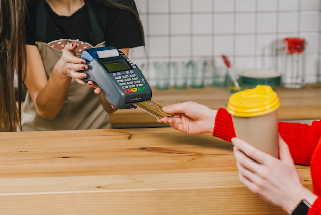 Crop client paying for drink in cafe Free Photo