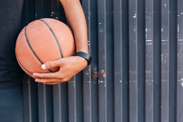 Crop close up hand holding basketball Free Photo