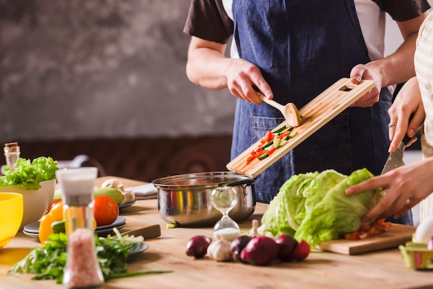 Crop couple cooking salad together Free Photo