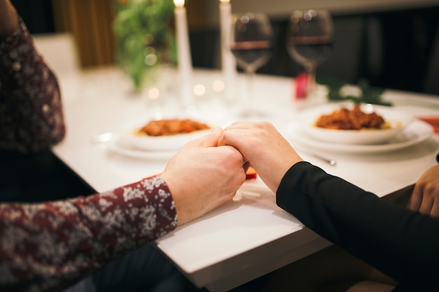 Crop couple holding hands on table Photo | Free Download