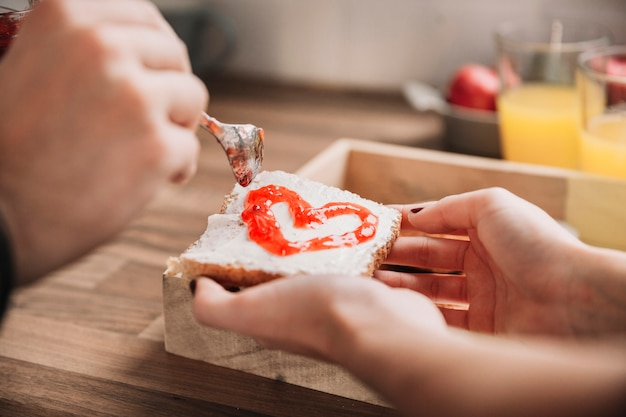 Crop couple making toast with jam Free Photo