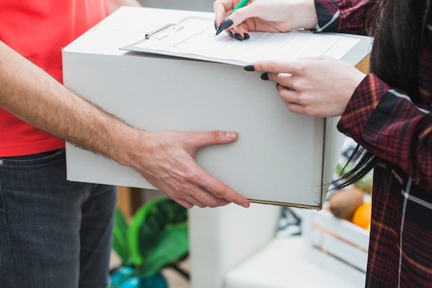 Crop courier and customer with parcel Free Photo