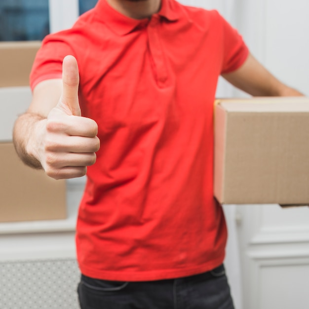 Crop courier gesturing thumb-up Free Photo