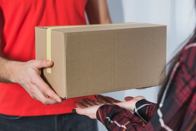 Crop courier giving parcel to woman Free Photo