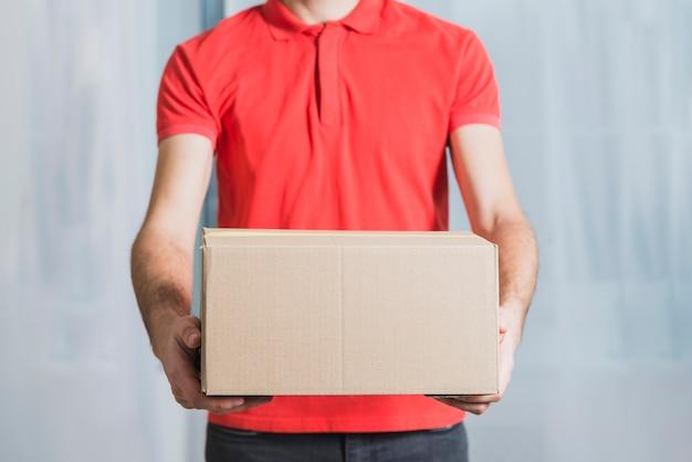 Crop delivery man showing parcel Premium Photo