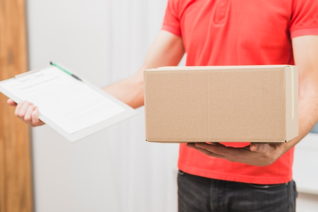 Crop delivery man with box and clipboard Free Photo