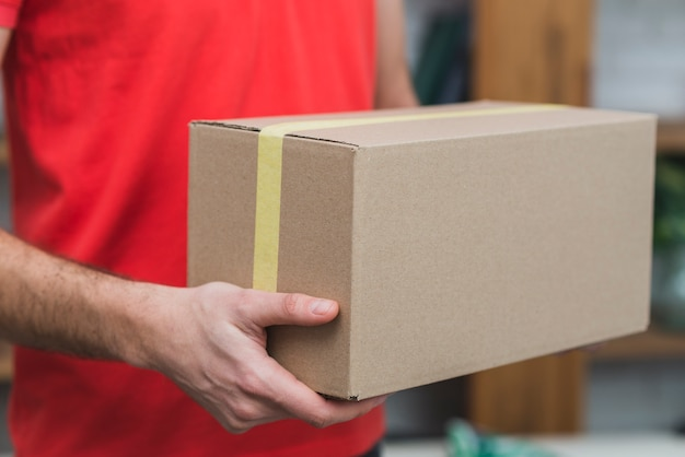 Crop delivery man with carton box Free Photo