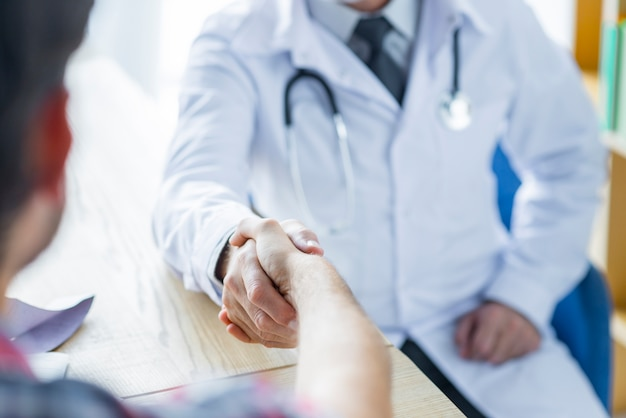 Crop doctor and patient shaking hands in office Free Photo