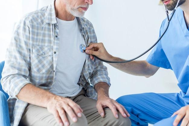 Crop doctor examining lungs of elderly patient Free Photo