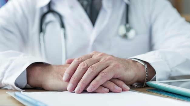 Урожай врач, держась за руки на столе Бесплатные Фотографии