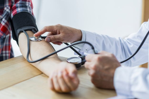 Crop doctor measuring blood pressure of patient Free Photo