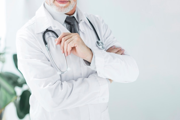 Crop doctor touching stethoscope Free Photo